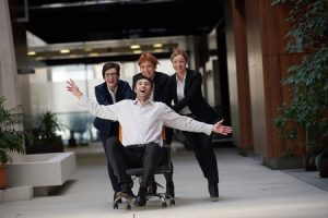 Three office workers having fun pushing another office worker in a wheeled chair